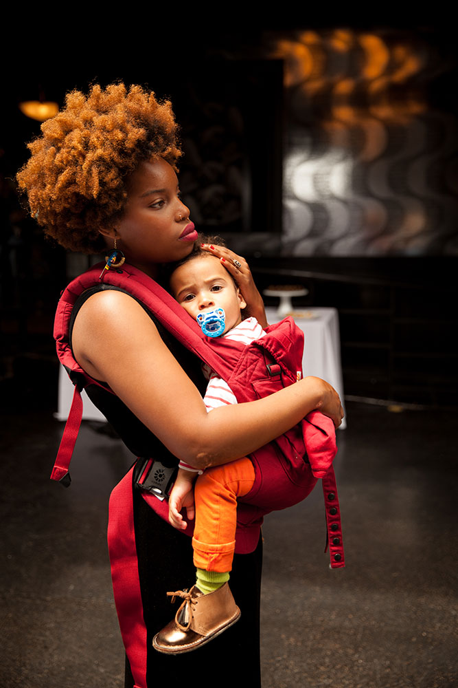 A Woman carries her baby in an Ergobaby Baby Carrier while traveling