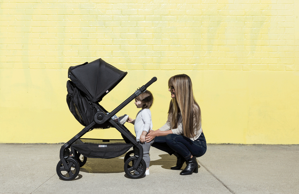 A baby faces her mom and sibling in a stroller