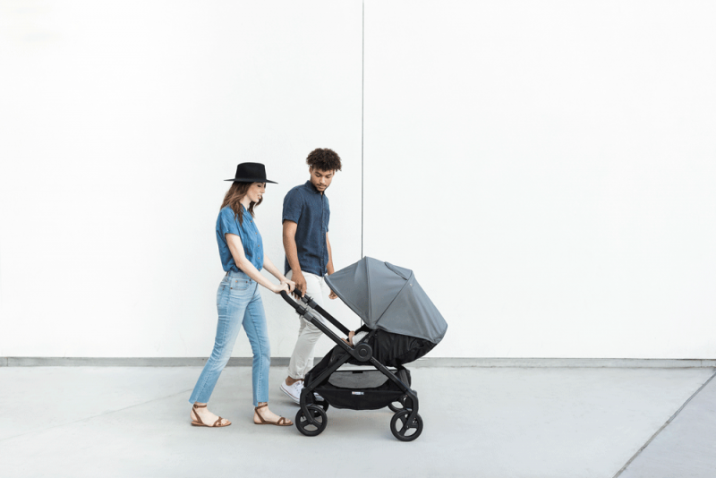 A baby faces parents in a stroller