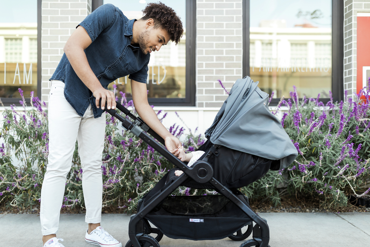 A nab reaches for his baby inside a 180 Reversible Stroller