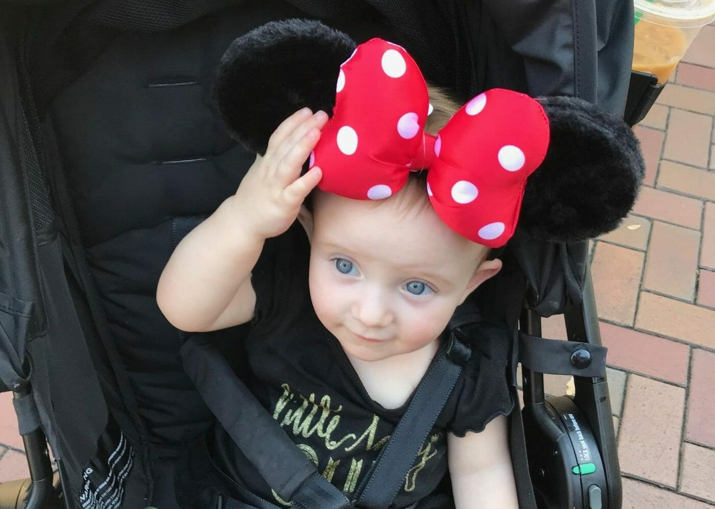 A baby sits in an Ergobaby stroller at Disneyland