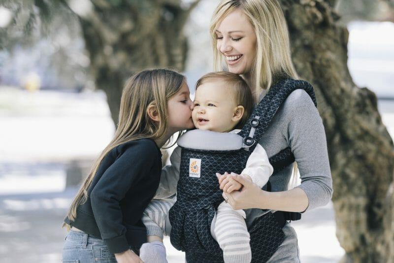 A girl kisses a baby facing forward in an Omni 360