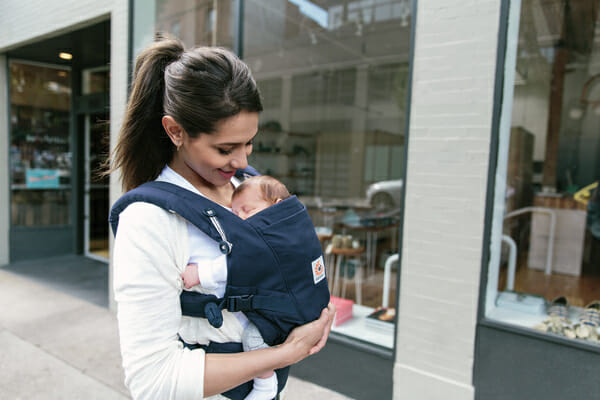 A woman with her baby in an Ergobaby Adapt Carrier