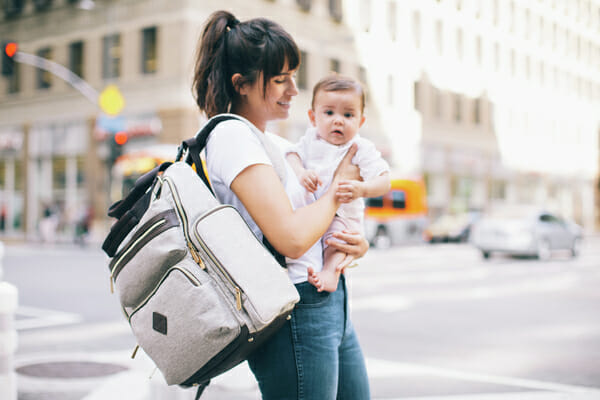 A woman outside with her baby and her Ergobaby Diaper Bag