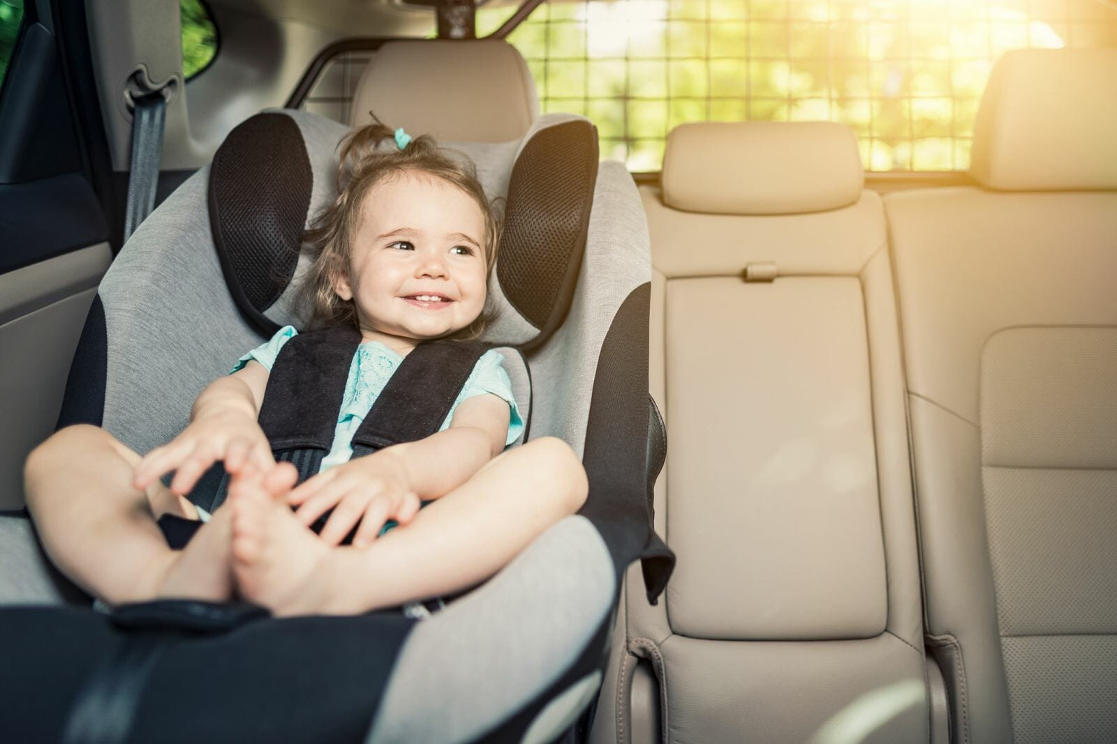 A toddler sits in her car seat