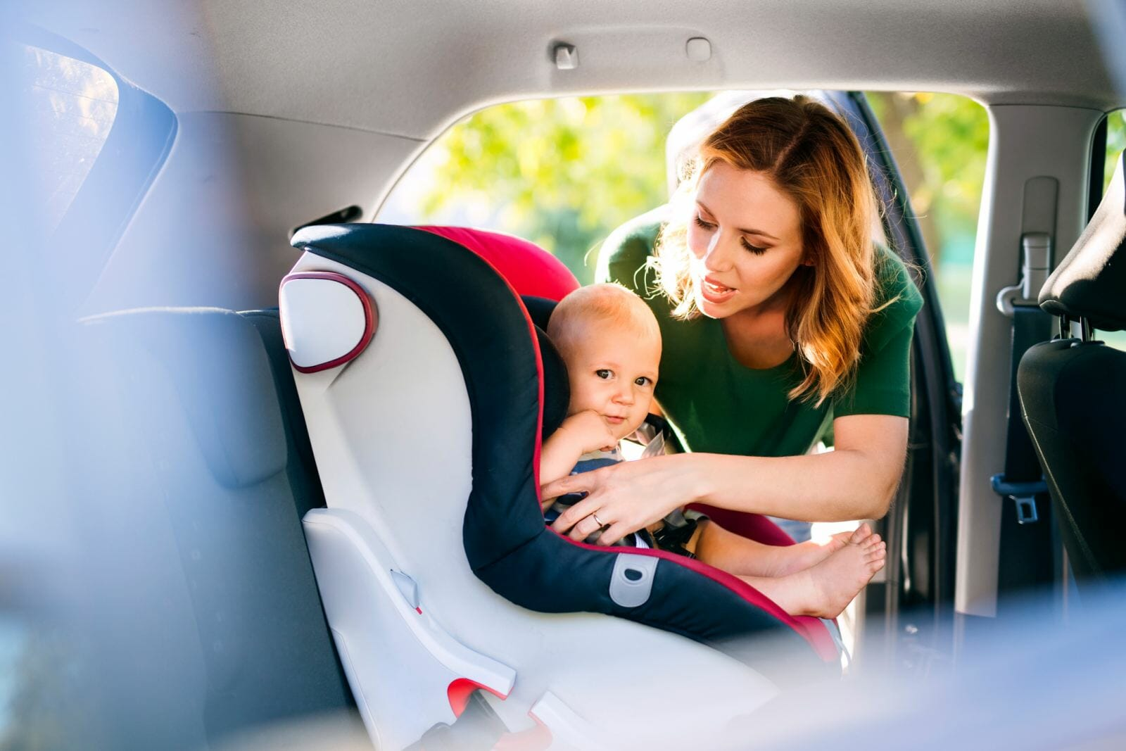 A mom helps her baby into a car seat