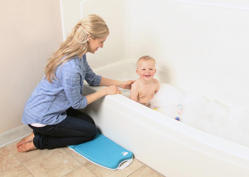 mother kneeling to bathe child