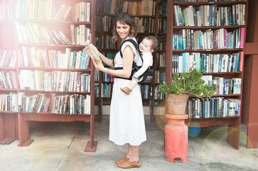 Mom in library with Ergobaby baby carrier
