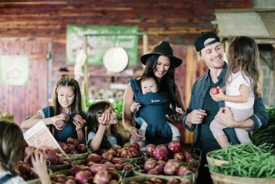 woman holding baby in Ergobaby carrier while shopping at the market with young family