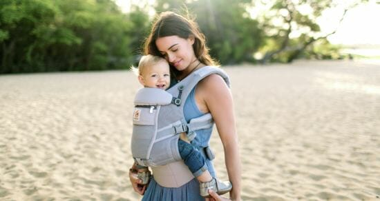 woman carrying baby on beach in Ergobaby carrier