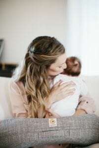 woman using Ergobaby Nursing pillow with baby
