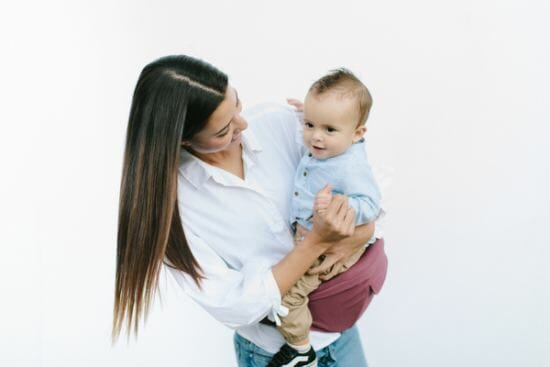 mom holding baby in hip seat carrier