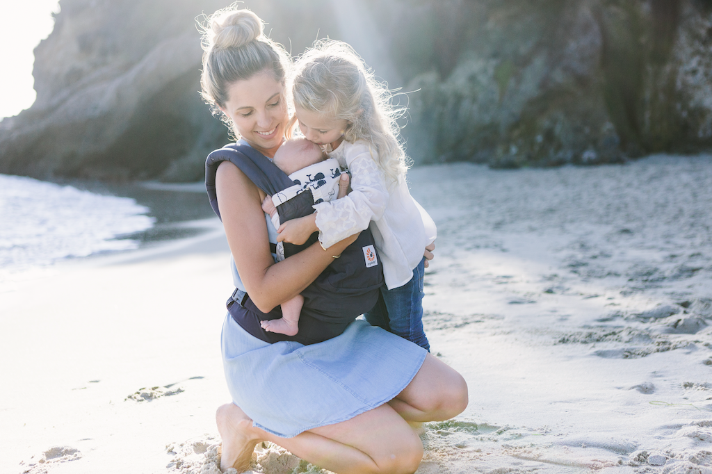 woman holding baby in original ergobaby carrier on beach