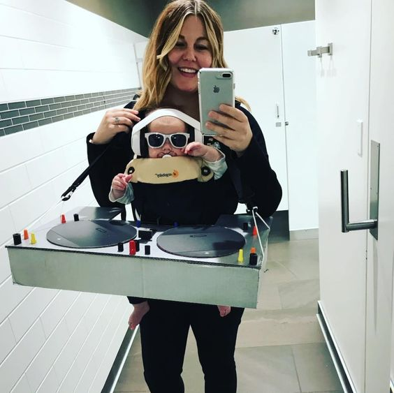mom holding baby in Ergobaby carrier dressed up as baby DJ